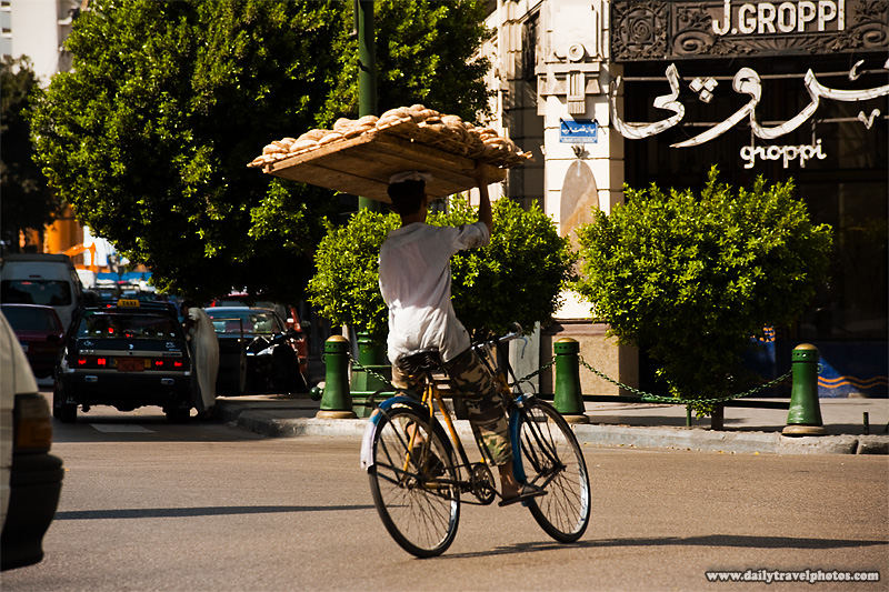 A bicycle bread delivery guy makes a turn after dodging a car - Cairo, Egypt - Daily Travel Photos