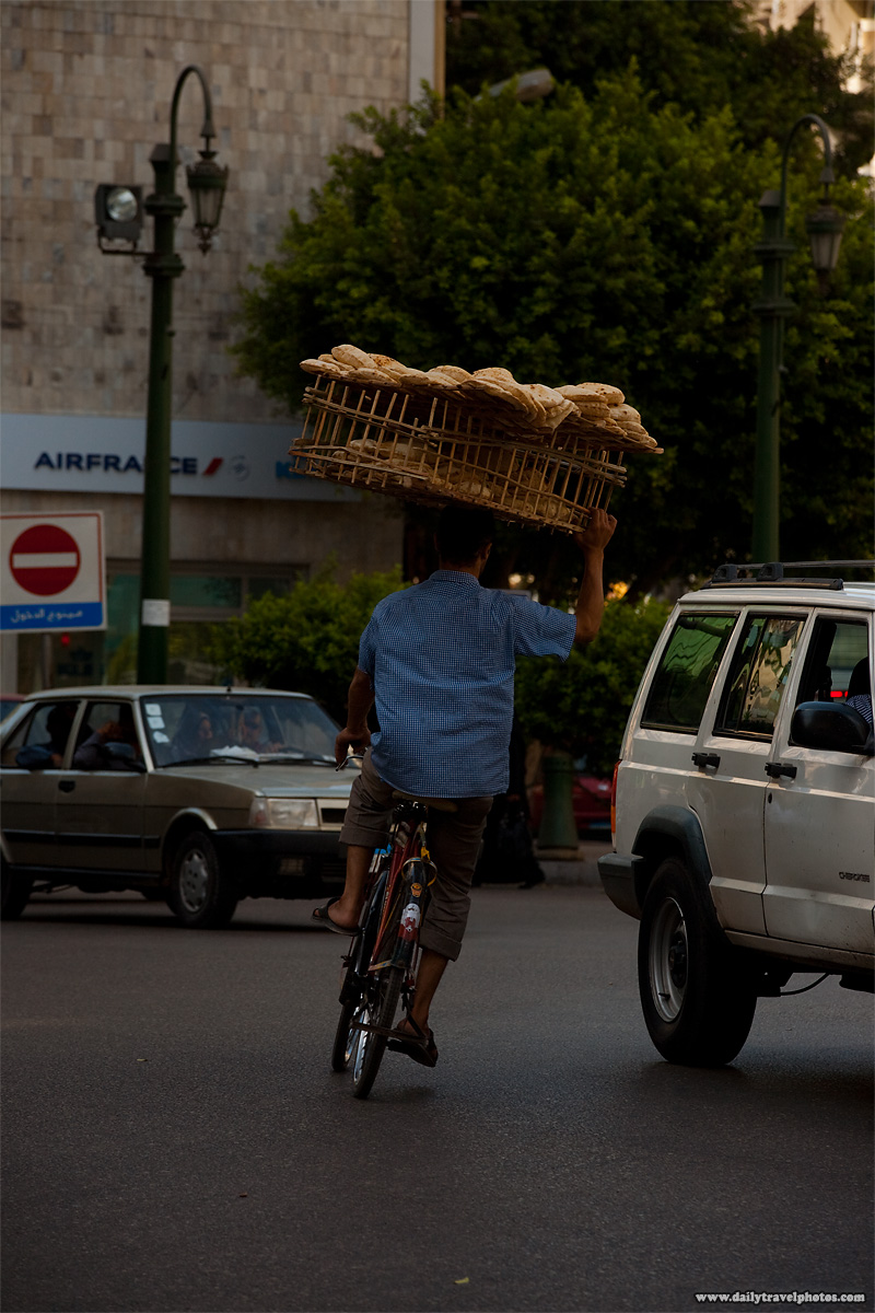A bicycle bread delivery guy ducks behind fast moving traffic in downtown Cairo - Cairo, Egypt - Daily Travel Photos