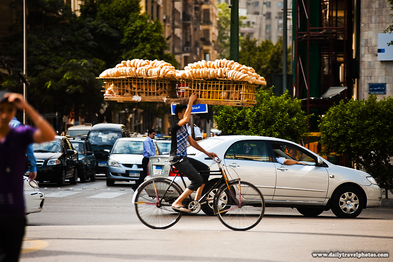 A bicycle bread delivery guy steadies a rack of bread with one hand - Cairo, Egypt - Daily Travel Photos