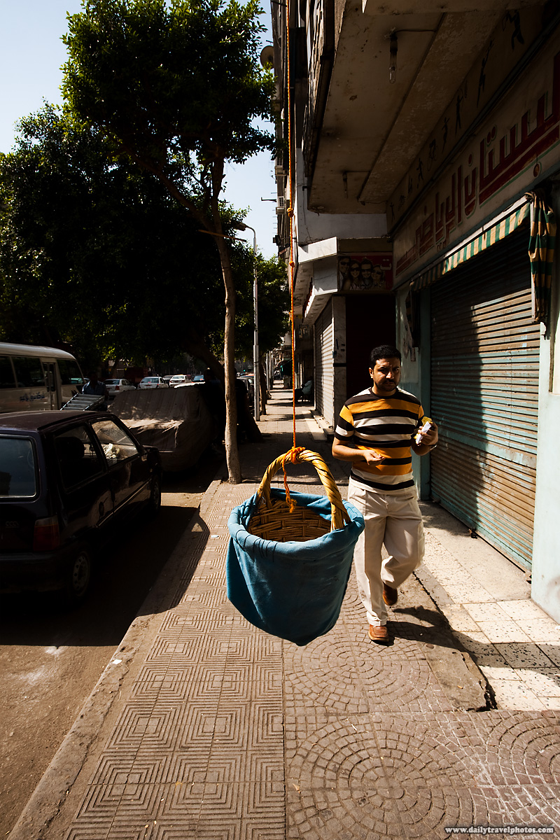 An Egyptian man walks by a hanging delivery basket on a narrow sidewalk - Cairo, Egypt - Daily Travel Photos