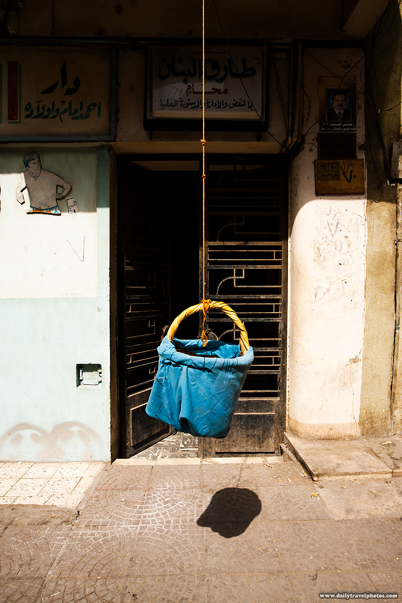 A hanging basket lowered from an apartment window - Cairo, Egypt - Daily Travel Photos