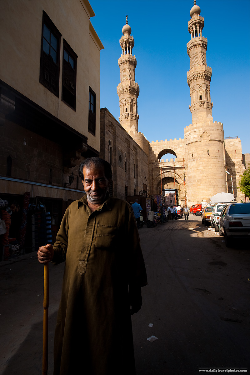 A Egyptian man stands with a cane in front of the Bab Zuweila gateway - Cairo, Egypt - Daily Travel Photos