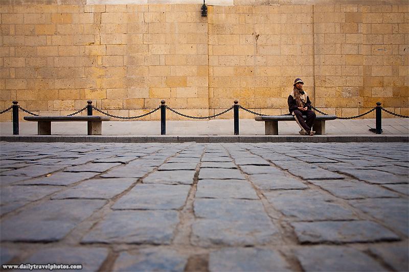 A street-cleaner rests on a bench in Islamic Cairo - Cairo, Egypt - Daily Travel Photos