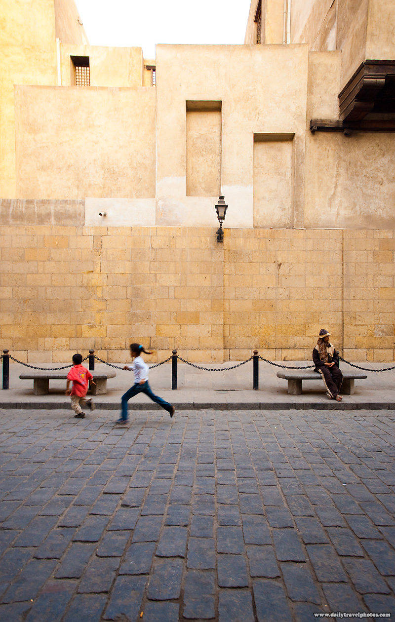 A street-sweeper rests undisturbed by children's horseplay - Cairo, Egypt - Daily Travel Photos