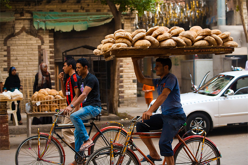 A bicycle bread delivery guy carries a rack of fresh bread on his head - Cairo, Egypt - Daily Travel Photos