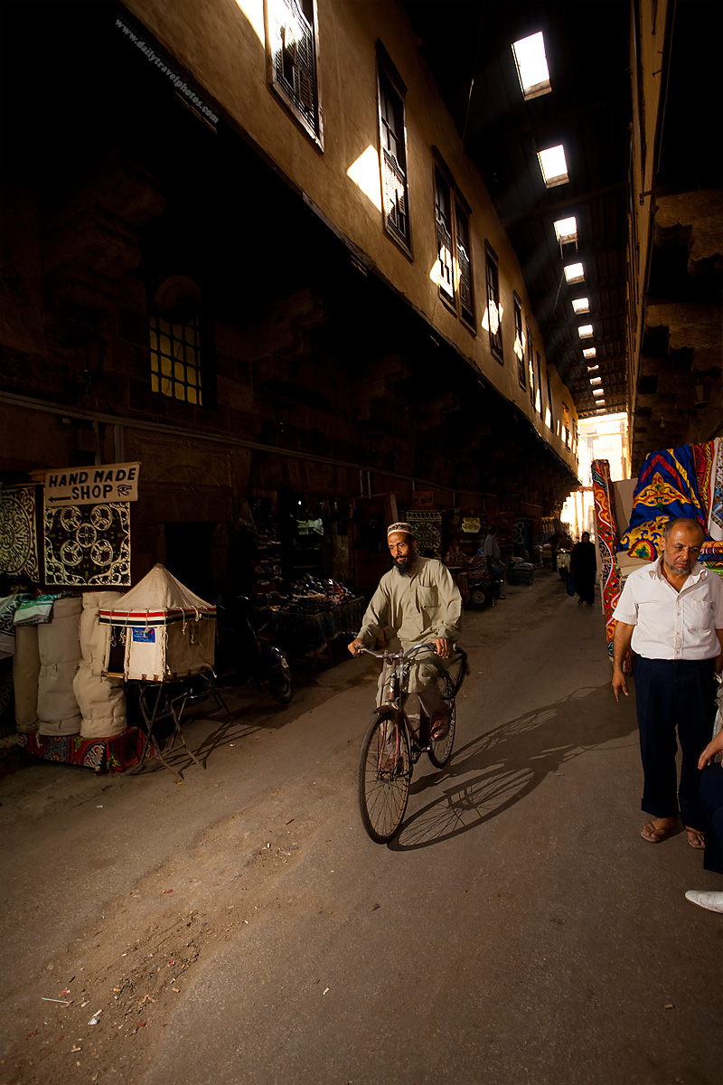 A Muslim man rides his bicycle back through the Bazaar of the Tentmakers - Cairo, Egypt - Daily Travel Photos