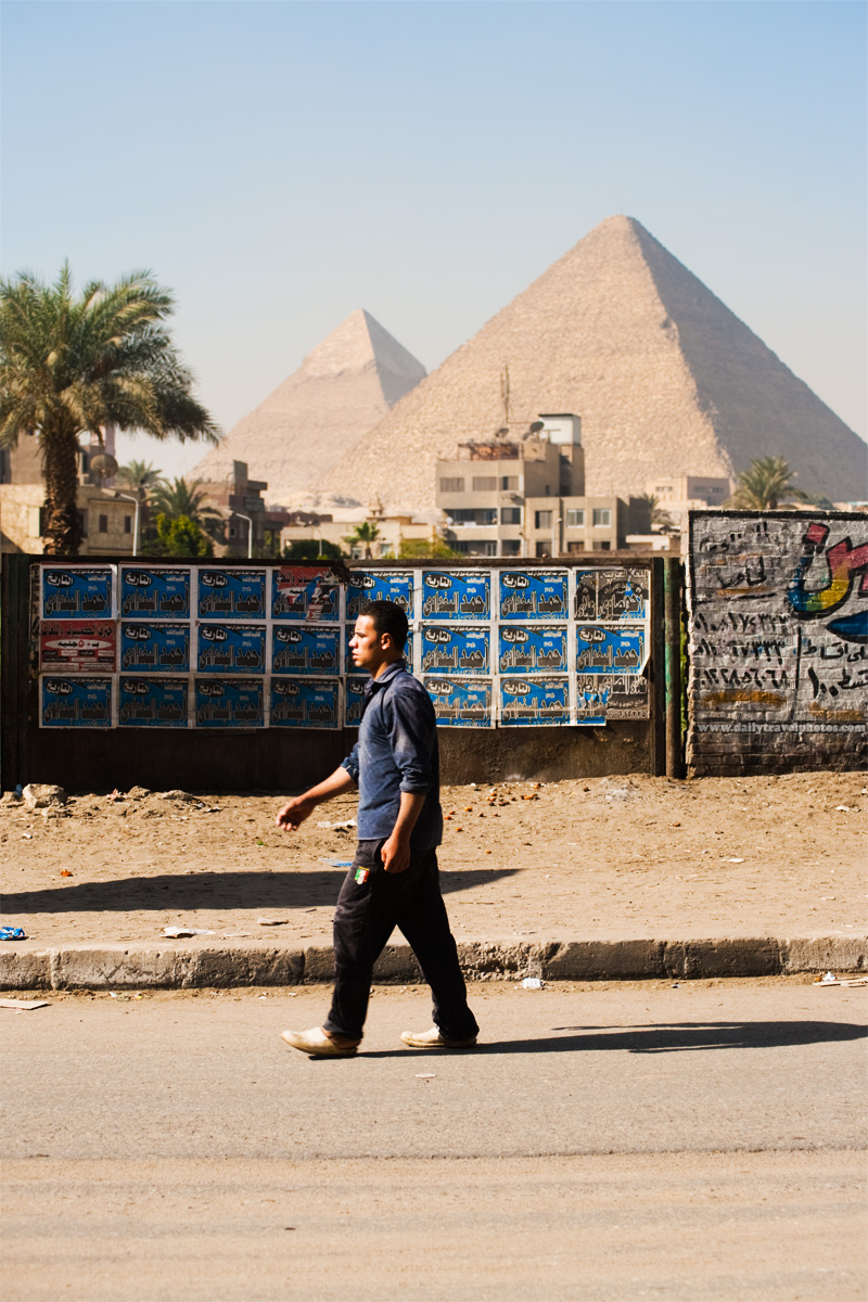 An Egyptian man walks on a road adjacent to the Great Pyramids of Giza - Cairo, Egypt - Daily Travel Photos
