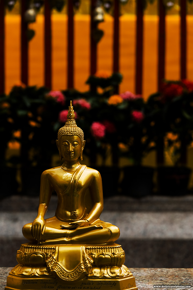 A small meditating golden Buddha statue in lotus position at Doi Suthep temple - Chiang Mai, Thailand - Daily Travel Photos