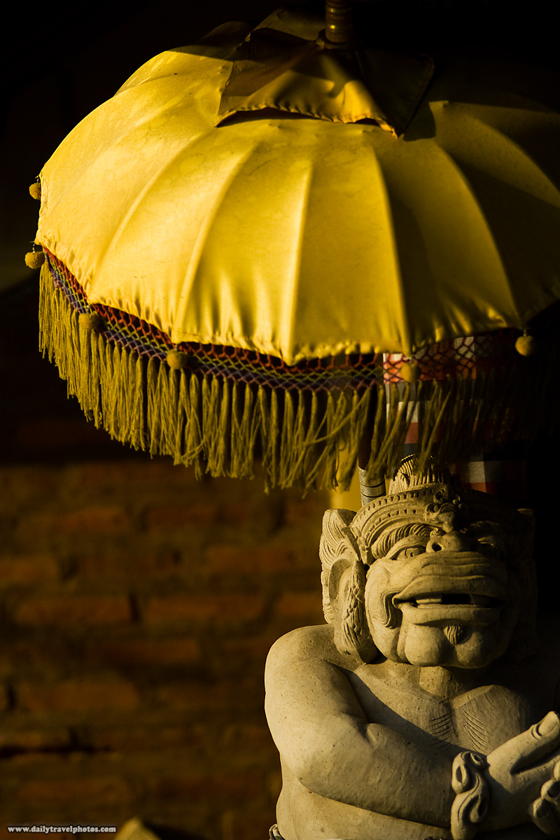 Balinese Statue Under Umbrella Hindu God Monster - Kuta, Bali, Indonesia - Daily Travel Photos