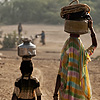 Village Life Photo: Mother and daughter balance pots on their heads to collect water at the village water tank.
