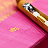 Gold Code Photo: A shuttle rests on an unfinished silk saree.