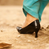 Off-Roading Photo: A high-heeled woman expertly navigates a typical unpaved Indian road.
