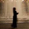 Water Works Photo: A female Arab tourist walks in front of a fountain at Kuala Lumpur City Center (KLCC).