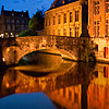 1614 | 1608 Photo: A canal reflects a bridge and traditional buildings in the historic center of Bruges.
