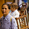 photo: Li'l Luggage - A grandmother carries a baby in a traditional wooden baby carrier.