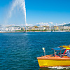 'Spensive City Photo: A yellow passenger taxi plies the pristine waters of Lake Geneva as jet d'Eau water fountain shoots into the sky.