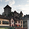 Riverfront Gourmands Photo: Tourists dine on the waterfront as the Annecy castle towers behind.