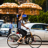 Amazing Acrobatics Photo: A bicycle bread delivery guy steadies a rack of bread with one hand through Cairo traffic.