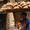 Starch Source Photo: A bicycle bread delivery guy carries a rack of fresh bread on his head.