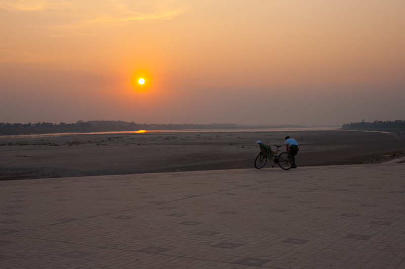 Laotian Bicyclist Mekong River Sunset Promenade - Vientiane, Laos - Daily Travel Photos
