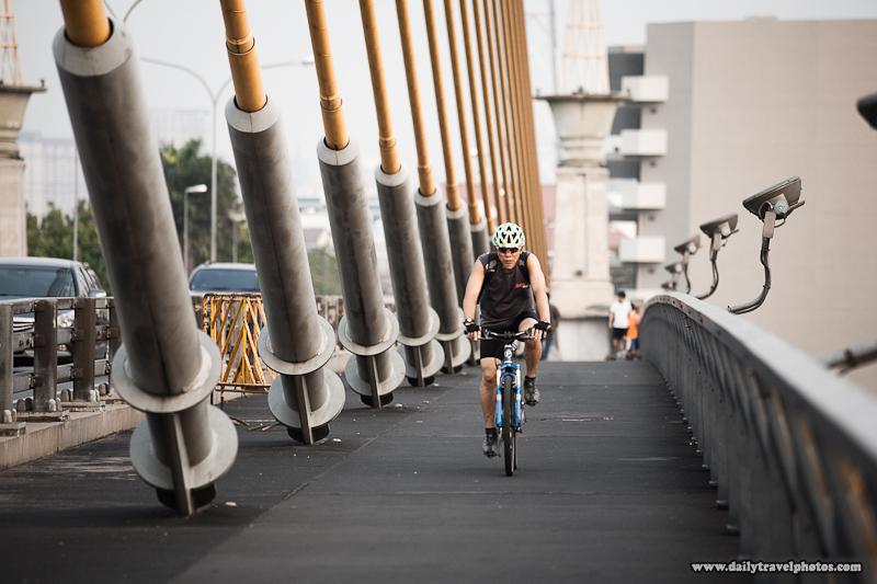 Stylized Bicyclist Rama VIII Bridge Evening Repetition Cables - Bangkok, Thailand - Daily Travel Photos