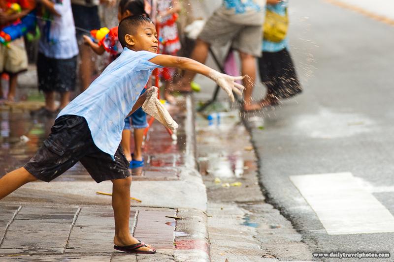 Young Thai Boy Throws Clumped Talcum Powder Roadside Songkran Festival - Bangkok, Thailand - Daily Travel Photos