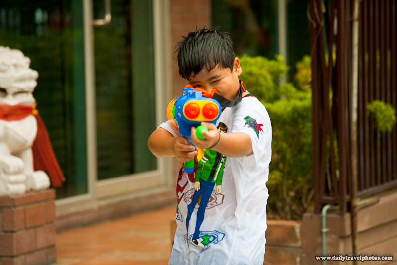 Young Thai Child Aiming Water Gun At Camera Songkran Festival - Bangkok, Thailand - Daily Travel Photos