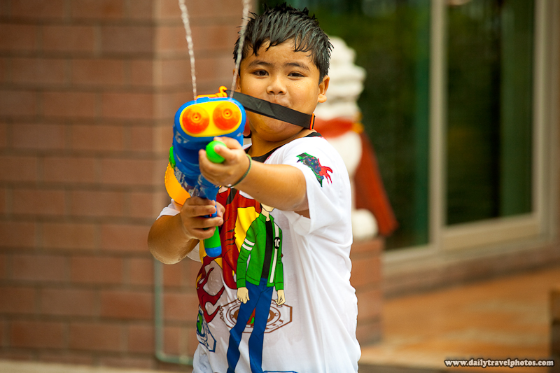 Young Thai Boy Shooting Water Gun At Camera Songkran Festival - Bangkok, Thailand - Daily Travel Photos