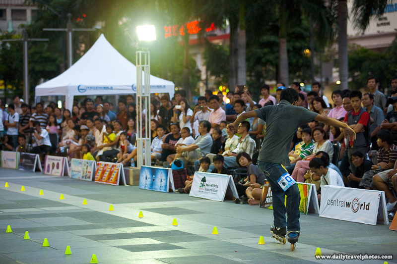 A Crowd Watches an Inline Skating Slalom Competitor Roll Sideways Slide Through Pylons at Central World - Bangkok, Thailand - Daily Travel Photos
