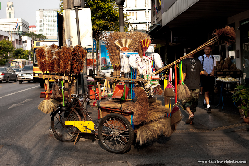 Bicycling Brush Mop Broom Salesman on Busy Street - Bangkok, Thailand - Daily Travel Photos