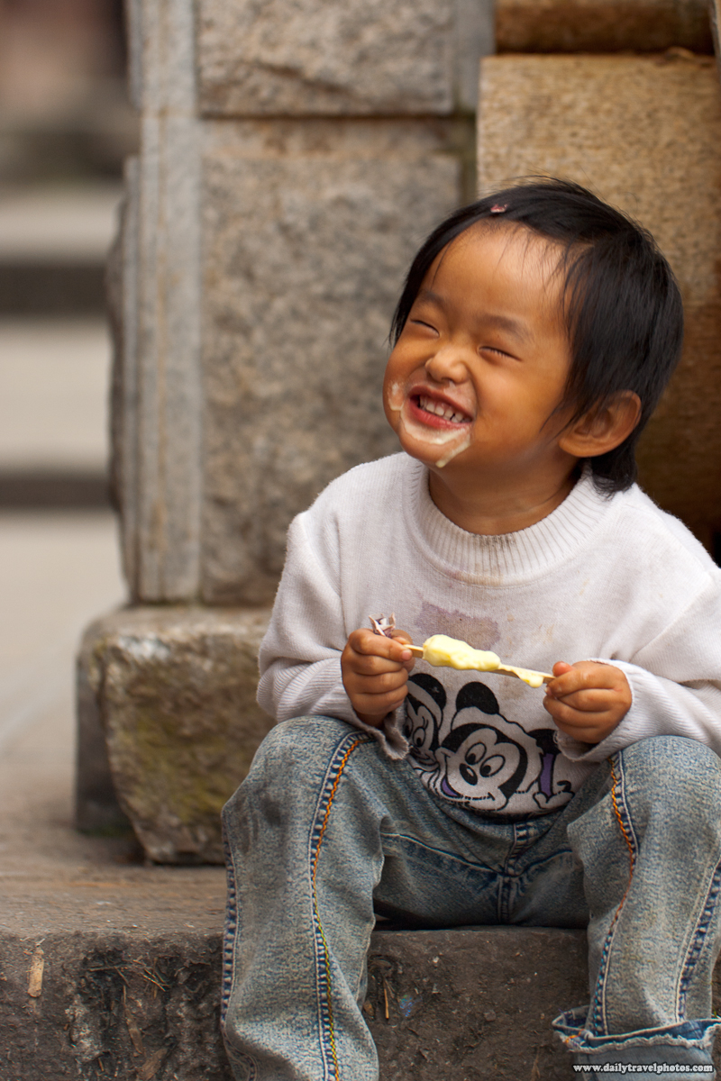 Young Chinese Girl Eating with Face full of Ice Cream - Dali, Yunnan, China - Daily Travel Photos