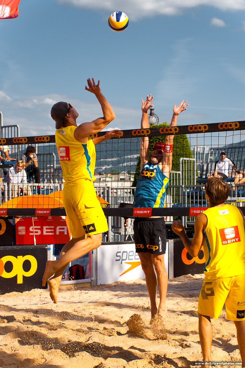 Coop Men's Beach Volleyball Player Jumping High to Spike Ball Over Opponent - Geneva, Switzerland - Daily Travel Photos