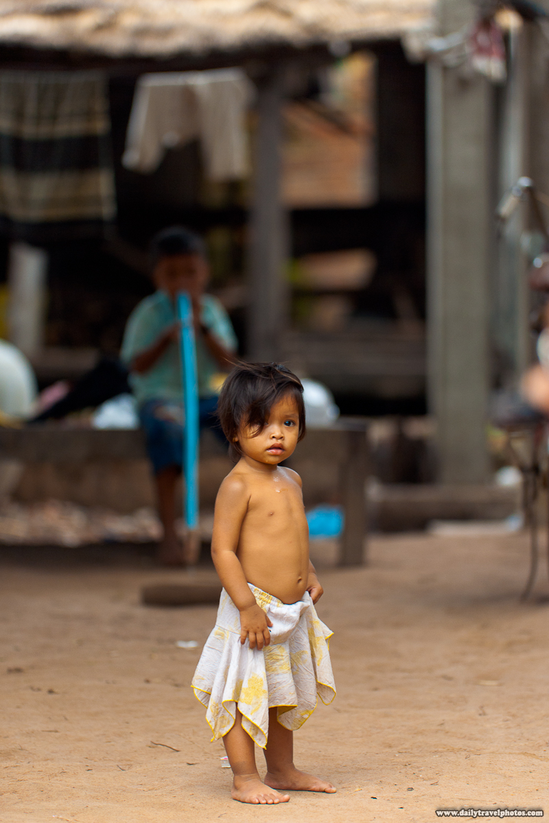 Beautiful Light on Cute Rural Cambodian Girl Standing Shirtless Shoeless in Dirt - Kompong Thom, Cambodia - Daily Travel Photos