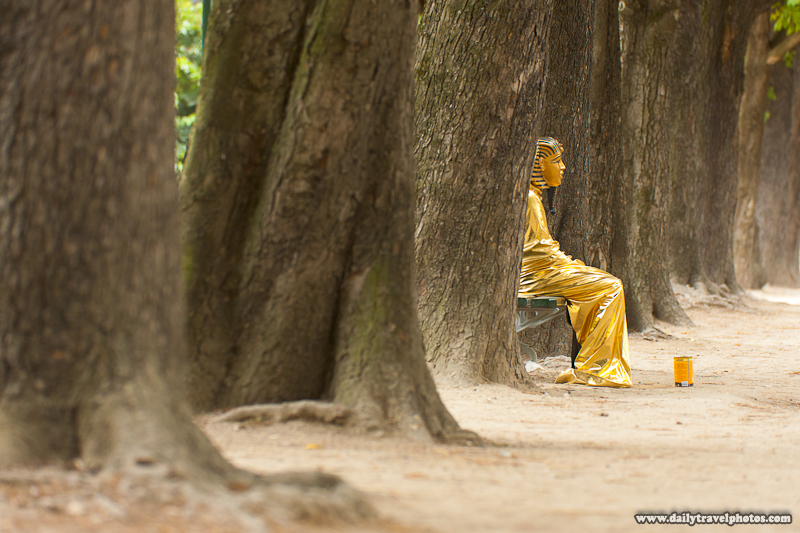 Street Performer Egyptian Sarcophagus Among Large Trees Sitting Alone - Paris, France - Daily Travel Photos