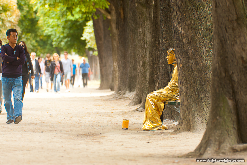 Street Performer Sitting on Wooded Bench on Champs Elysees Dressed as Golden Egyptian Sarcophagus - Paris, France - Daily Travel Photos