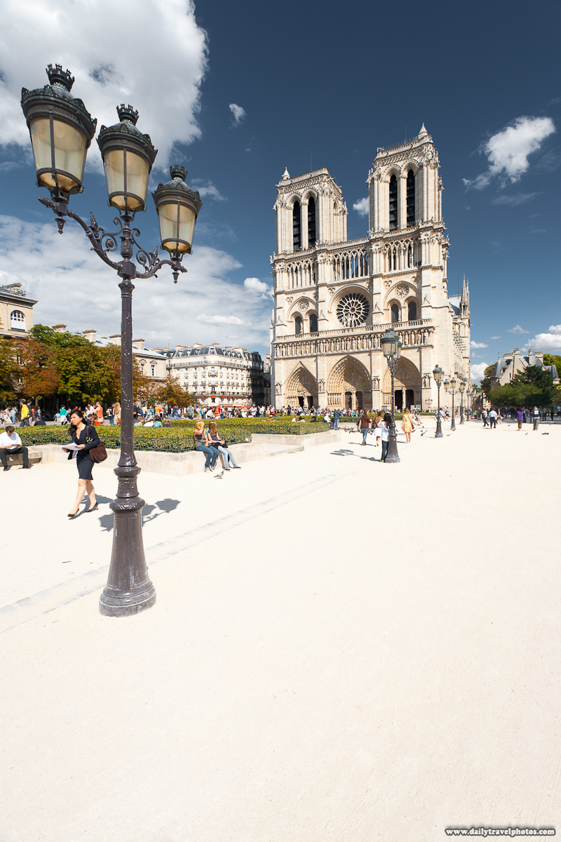 Tourists Milling Around Notre Dame Cathedral With Row of Old Street Lights - Paris, France - Daily Travel Photos