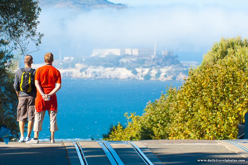 Tourists Looking at Far Away Alcatraz Prison View on Hyde Street - San Francisco, California, USA - Daily Travel Photos