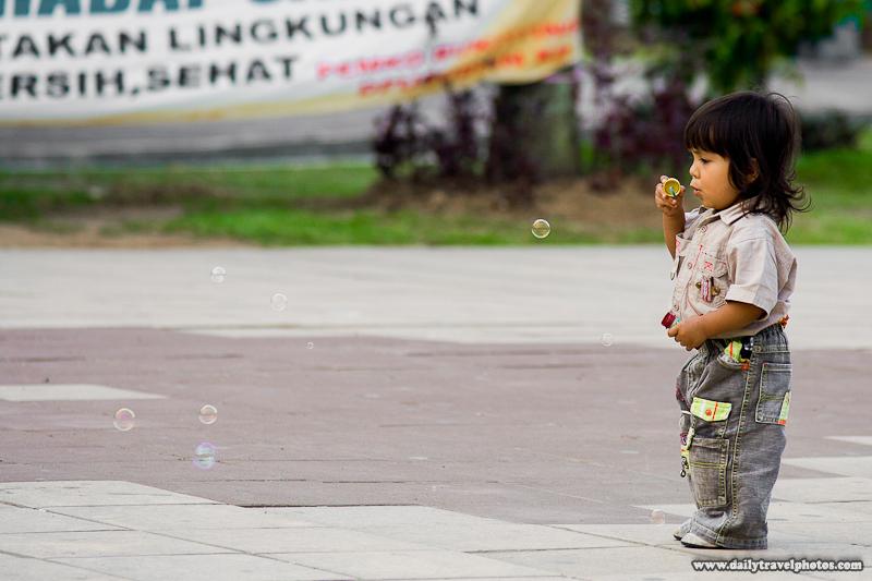 Young Indonesian Child Blowing Bubbles at Park - Bukittinggi, Sumatra, Indonesia - Daily Travel Photos