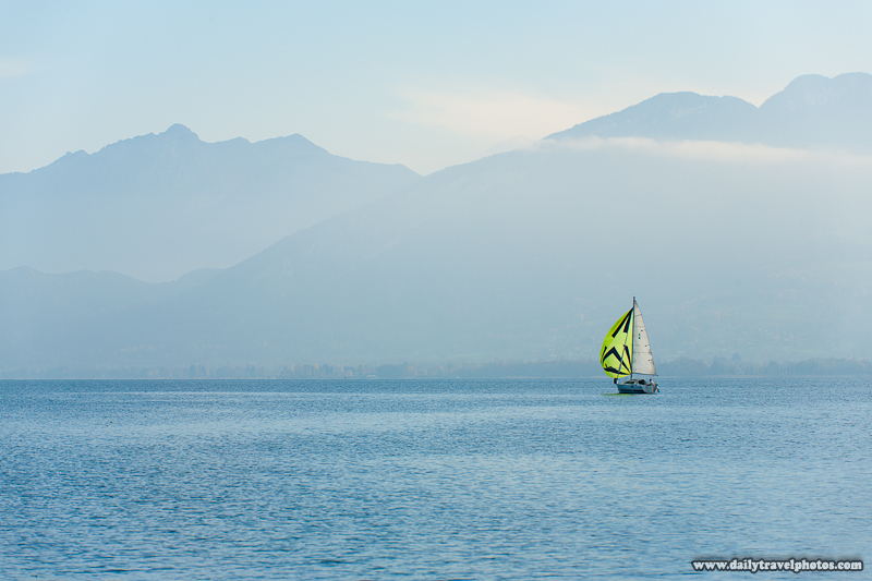 Lone Sailboat on Annecy Lake with Mountainous Background - Annecy, Haute-Savoie, France - Daily Travel Photos
