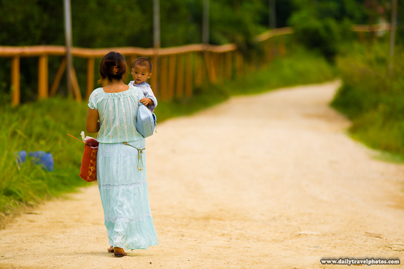 Mother Carrying Son Walking Down Long Dirt Road in Borneo - Kinabatangan, Sabah, Malaysia - Daily Travel Photos