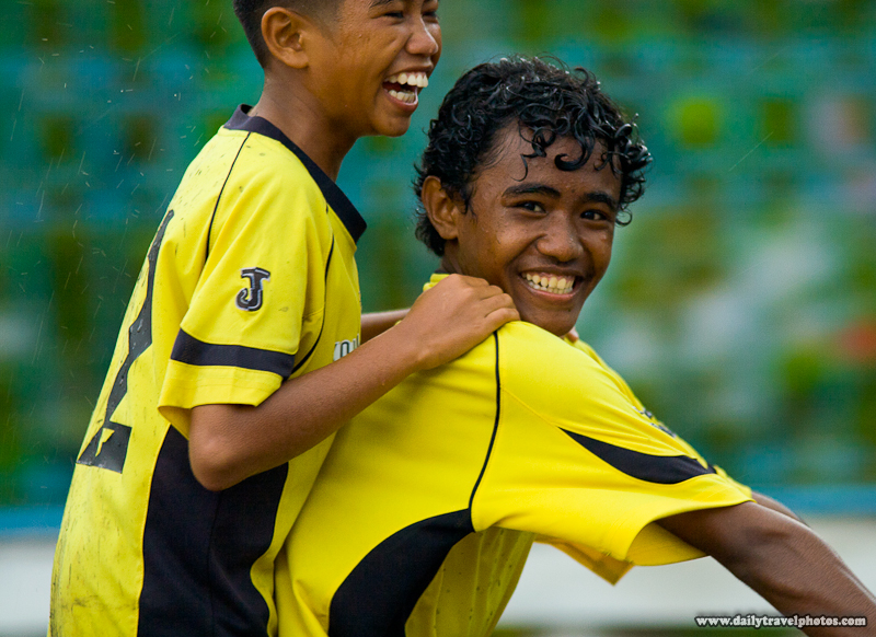 Laughing Young Boys Ride Bicycle in Rain - Dili, East Timor - Daily Travel Photos