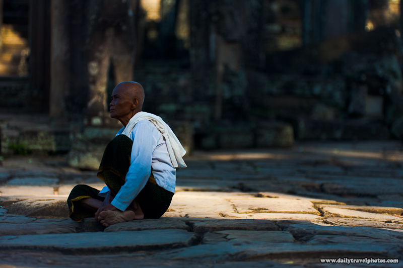 Female Buddhist Monk Sits at Bayon Temple in Angkor Wat - Siem Reap, Cambodia - Daily Travel Photos