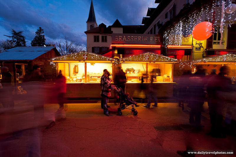 Tourists Walking in Front of Cheese Chalet in Christmas Market at Dusk - Annecy, Haute-Savoie, France - Daily Travel Photos