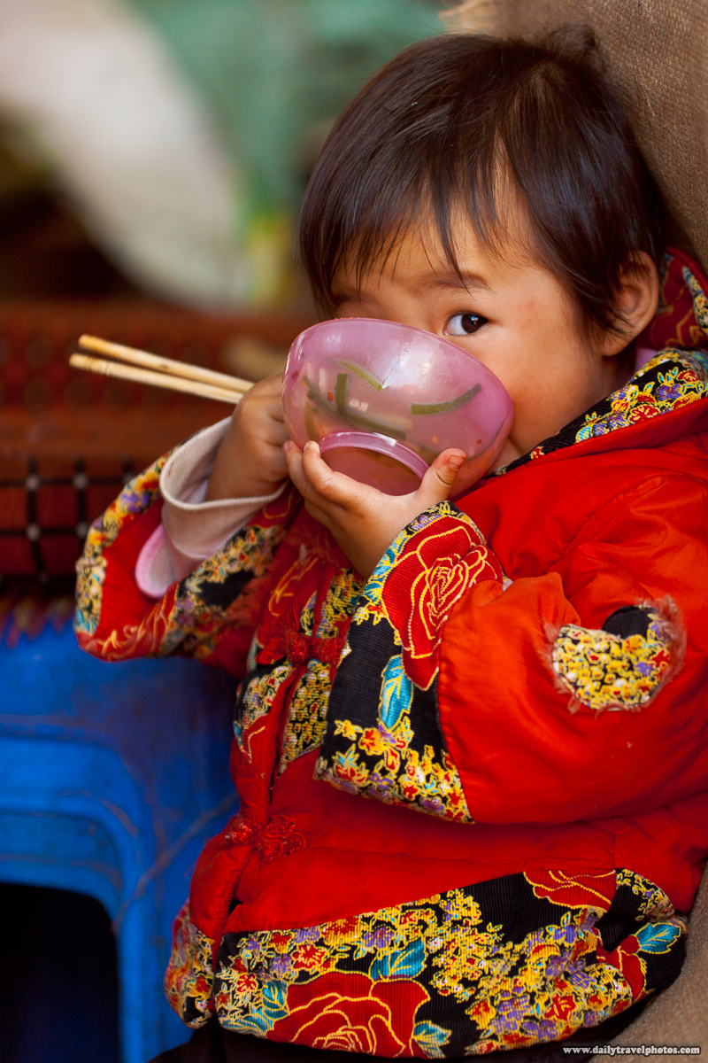 Young Chinese Girl Eats with Face Inside Bowl and Chopsticks with Wary Eye - Lijiang, Yunnan, China - Daily Travel Photos