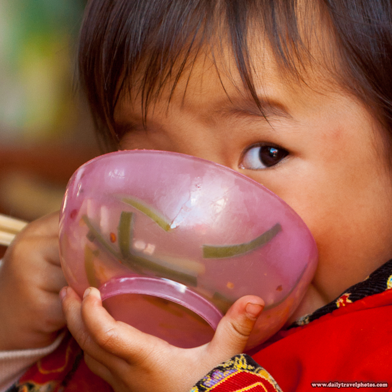 Baby Chinese Girl Eating with Face in Bowl - Lijiang, Yunnan, China - Daily Travel Photos