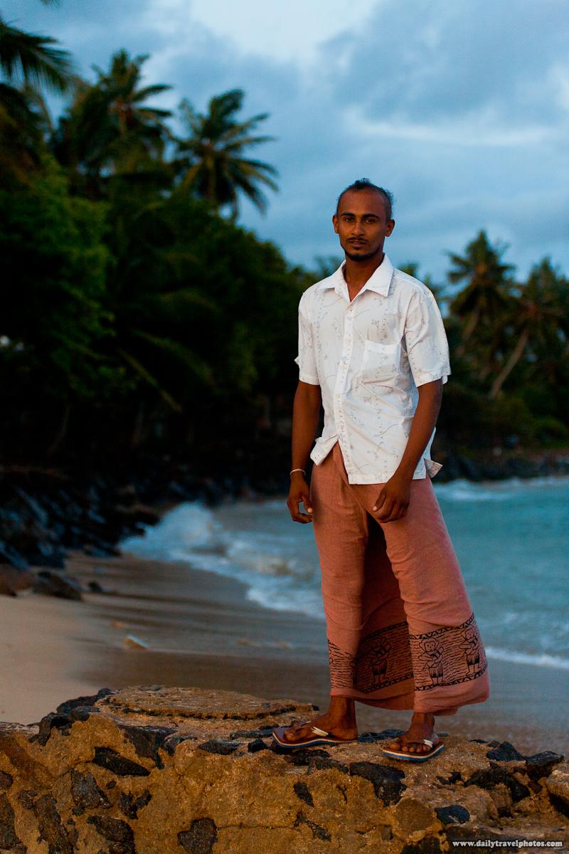 Sri Lankan Fisherman in Lungi Standing on Rock on the Beach - Mirissa, Sri Lanka - Daily Travel Photos