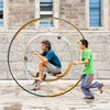 "photo: Single Wheeled Bicycle - An Italian tourist attempts to ride, with assistance, a unique, single-wheel ""bicycle"" (ARCHIVED PHOTO on the weekends - originally photographed 2007/06/09)."