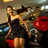 Motorcycle Models (Red) Photo: A classy Thai model shows off the latest in Piaggio motorcycles at Central World Mall in Bangkok.