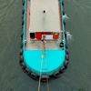 Tugboat Shipping Barge Photo: A tugboat lumbers up-river, seen from a top-down perspective on the Chao Phraya river in Bangkok.