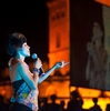 Female Thai Singer Photo: A female Thai singer is seen projected onto a TV screen in the background at an open-air performance in Bangkok.